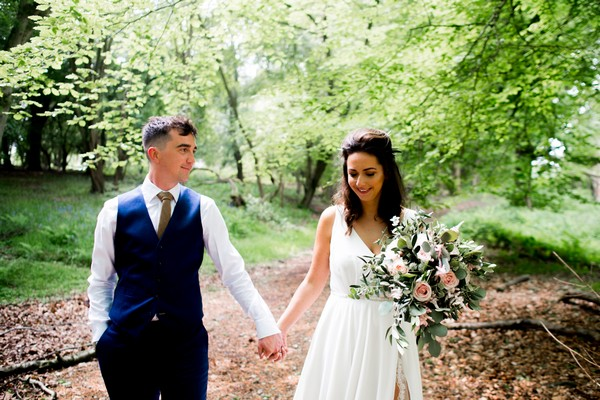 Bride and groom holding hands as they walk through woodland - Picture by Nicola Norton Photography