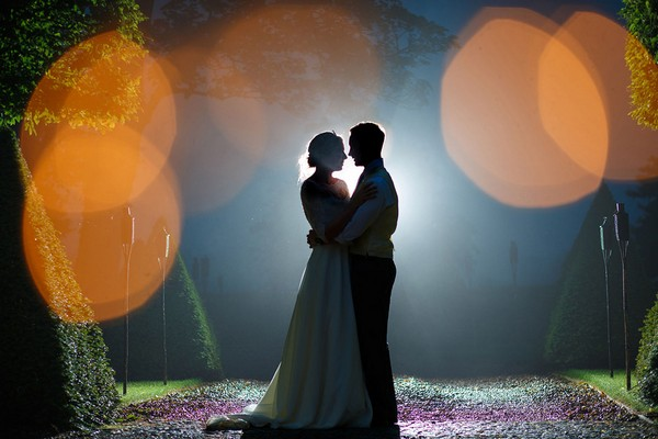 Bride and groom on path at night with light shining behind their heads - Picture by Photography by Suzanne Fossey