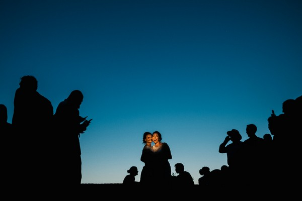 Two brides surrounded by silhouettes of wedding guests - Picture by Emma and Rich