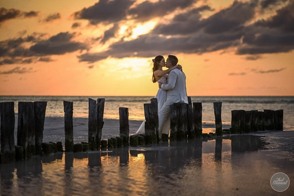 Bride and groom kissing on beach by sea at sunset - Picture by That Moment Photo