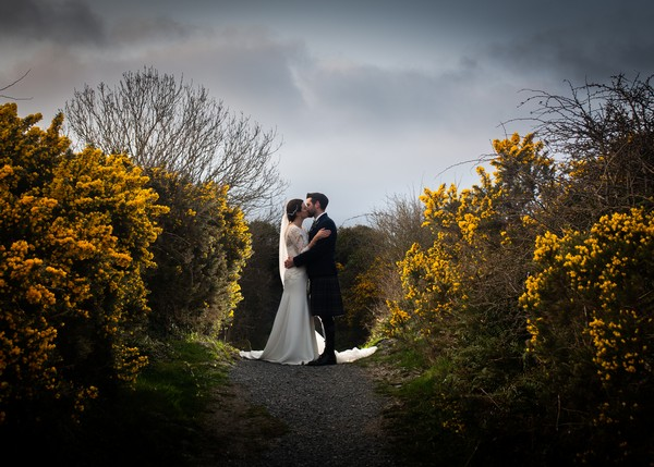 Bride and groom kissing on path surrounded by bushes - Picture by Giles Atkinson Photography