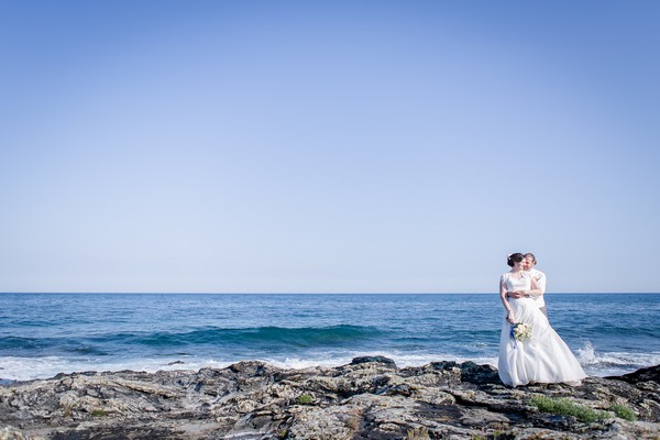 Bride and groom standing on rocks by the sea - Picture by Brian Robinson Photography