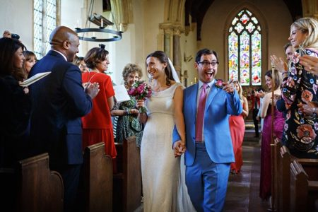 Groom pointing at wedding guest with big smile on his face as he leaves wedding ceremony with bride - Picture by Duncan Kerridge Photography