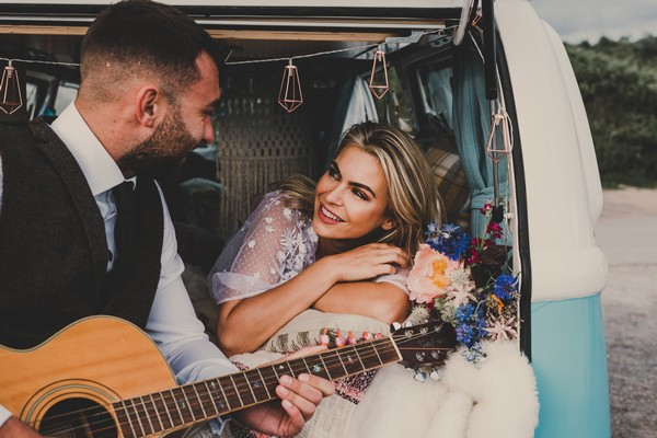 Bride sitting on back of camper van as groom plays guitar - Picture by Jade Maguire Photography