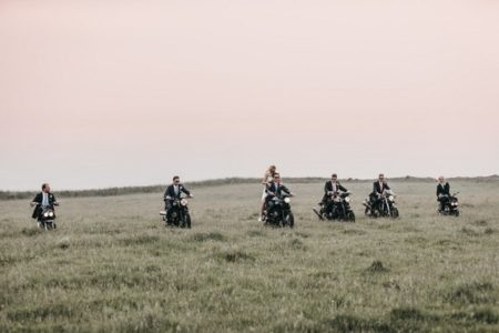 Bride, groom and groomsmen riding motorbikes across a field - Picture by Ben Wigglesworth Photography