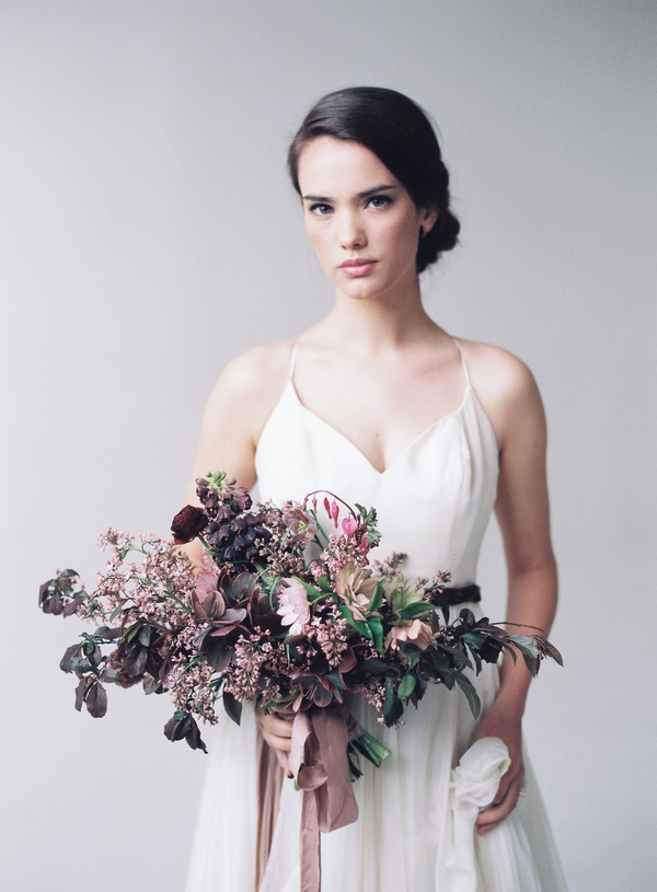 Bride holding bridal bouquet with mauve flowers