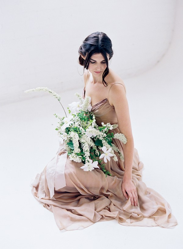 Bride sitting on floor wearing blush dress and holding white and green bouquet