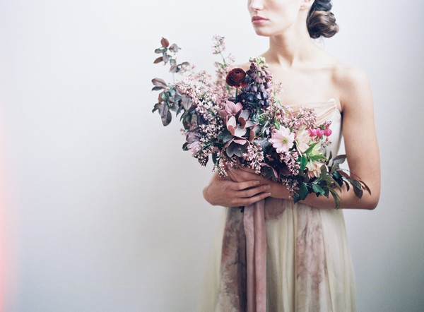 Bride holding large bouquet with mauve and blush flowers and foliage