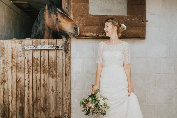 Bride standing next to horse in stable