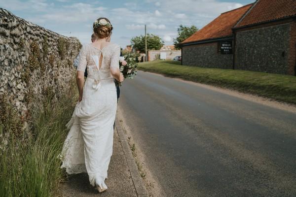Bride and groom walking by side of road
