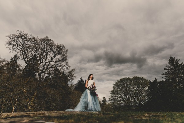 Bride standing on hill in Goyt Valley