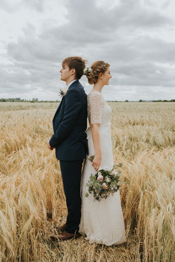 Bride and groom standing back to back in cornfield