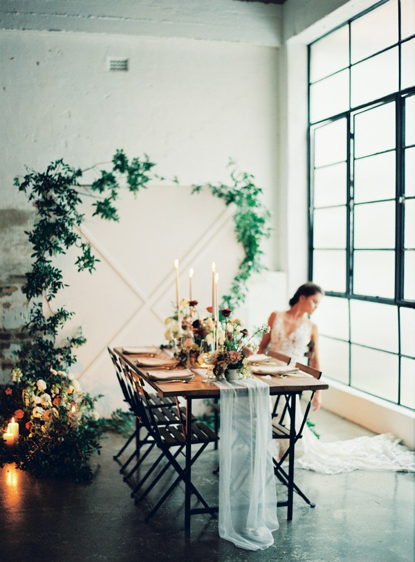 Bride sitting at wedding table in urban loft space