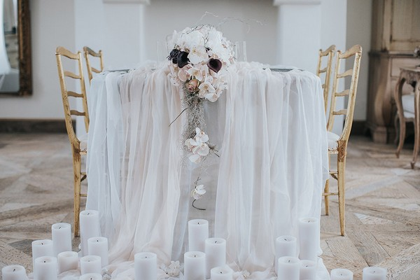 Candles on tablecloth draped off of table