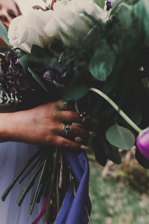 Hand with rings holding wedding bouquet