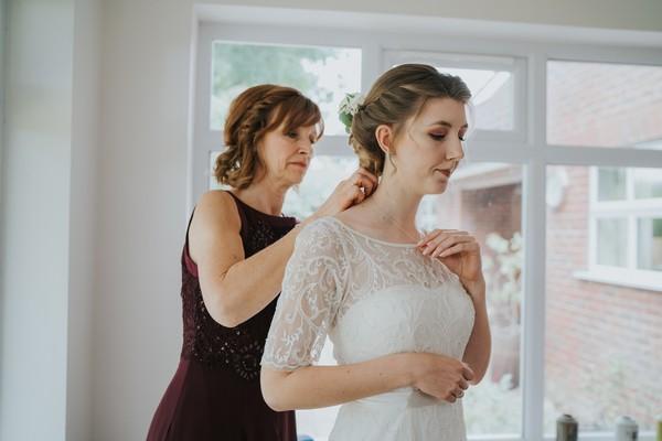 Bride's mother fastening bride's necklace