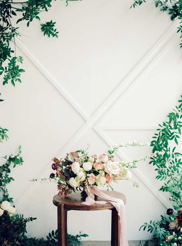 Wedding bouquet n small table in front of foliage backdrop