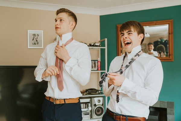 Groom and groomsmen putting on ties