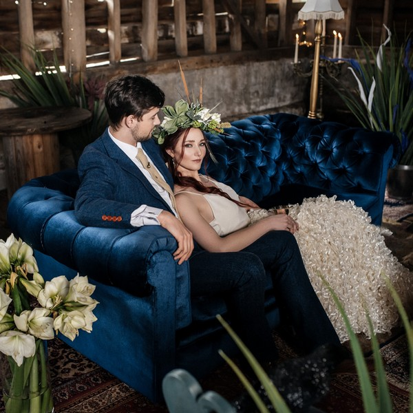 Bride and groom sitting on blue Chesterfield sofa available to hire from from The Prop Factory