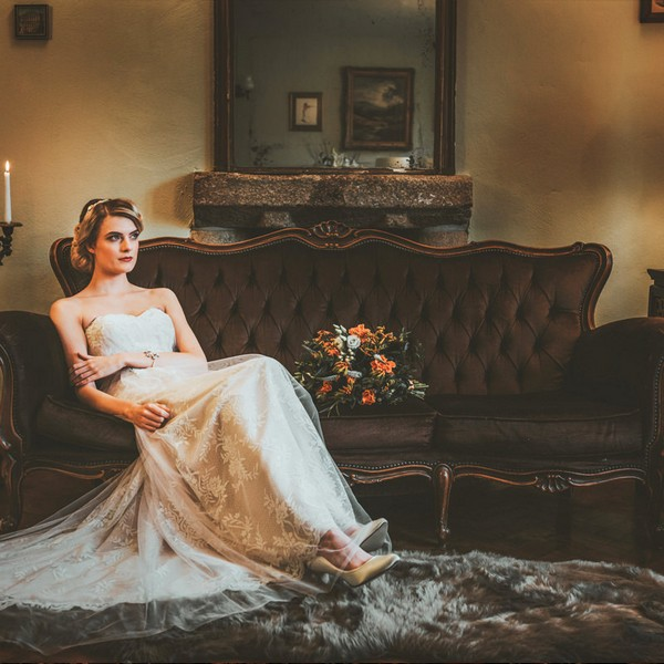 Bride sitting on chocolate coloured sofa available to hire from from The Prop Factory