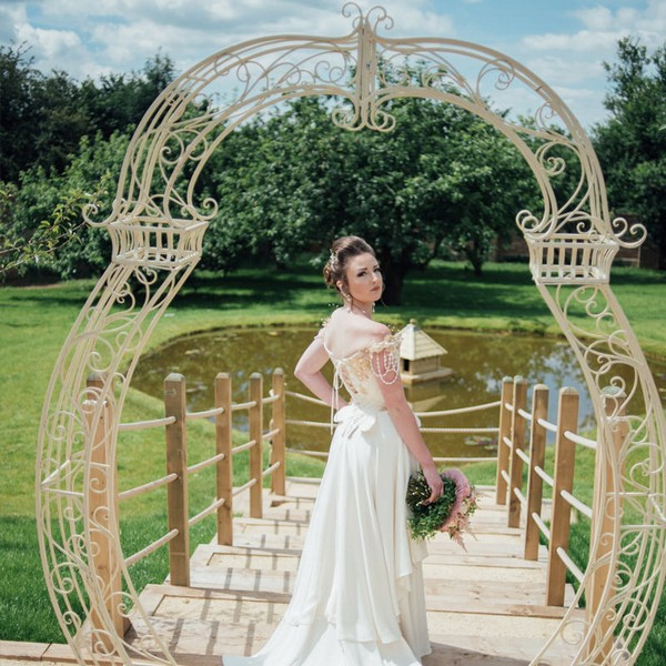 Bride under cream arch available to hire from from The Prop Factory