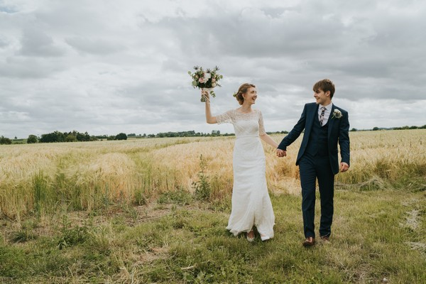 Bride holding bouquet in air as she walks in field with groom