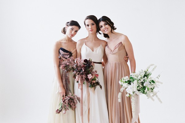 Three brides in white and blush wedding dresses holding bouquets
