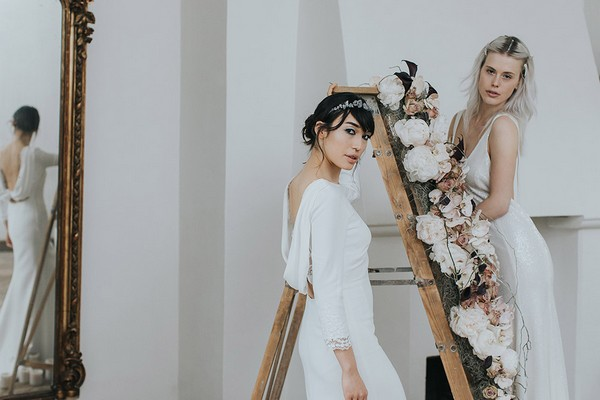 Two brides by ladder covered in flowers