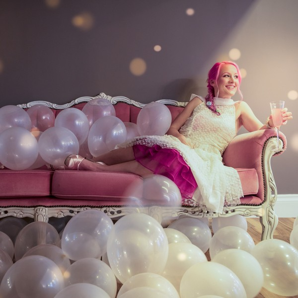 Bride sitting on pink sofa available to hire from from The Prop Factory