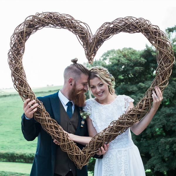 Bride and groom holding up willow heart available to hire from from The Prop Factory