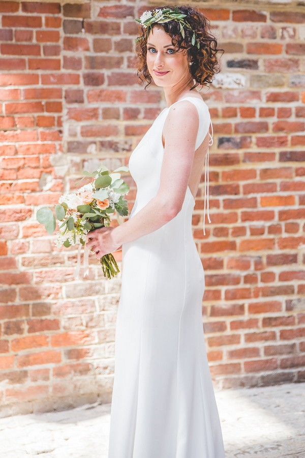 Bride holding bouquet in front of brick wall