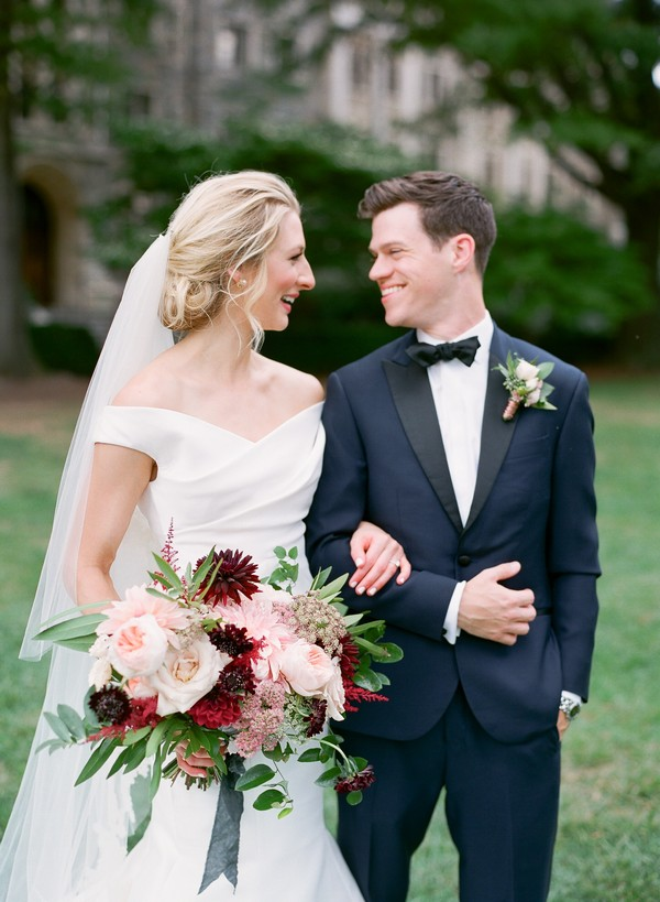 Bride and groom with linked arms smiling at each other