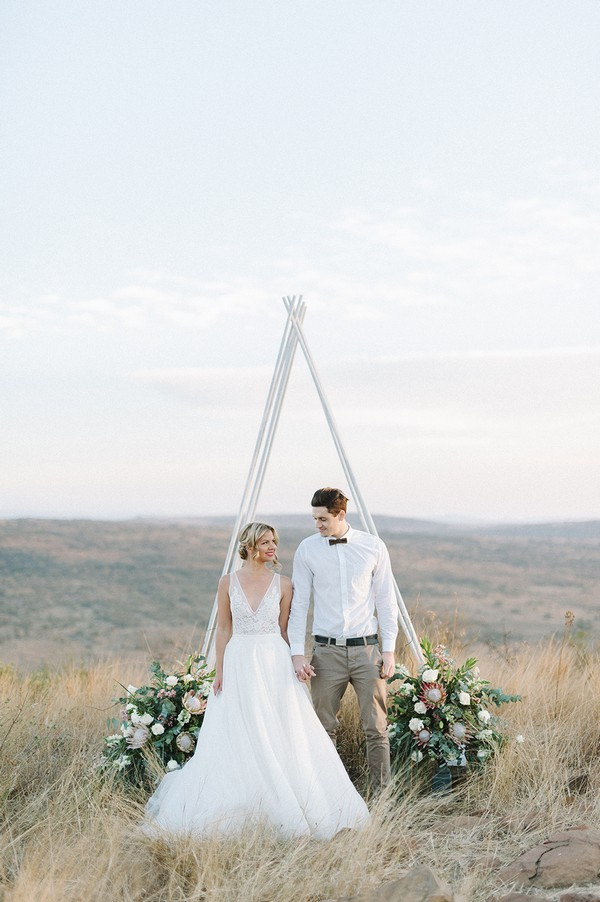 Bride and groom standing in front of tipi style ceremony arch