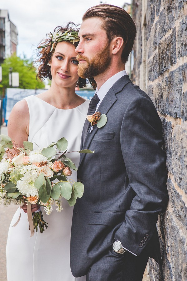 Bride and groom standing against brick wall