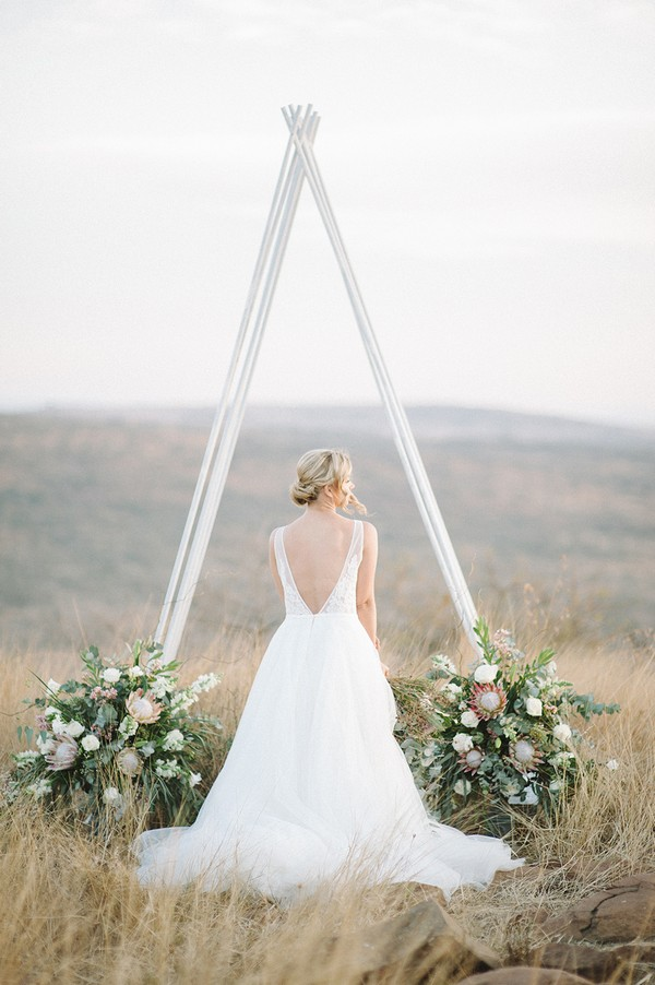 Bride standing in front of tipi style ceremony arch