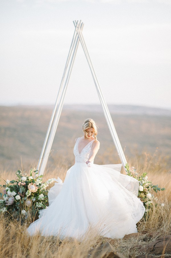 Bride twirling in front of tipi style ceremony arch