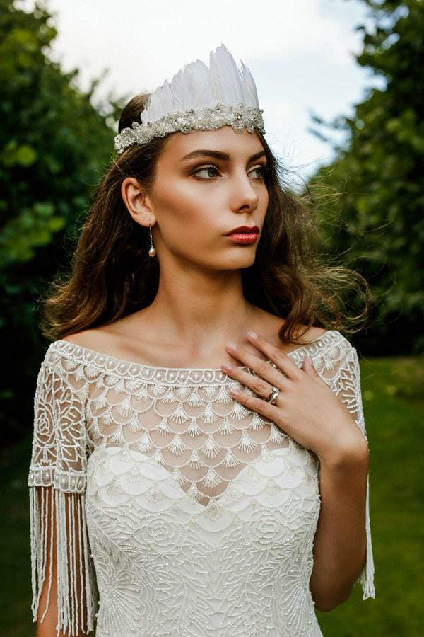 Bride wearing feather headpiece and wedding dress with tassels and piped detail