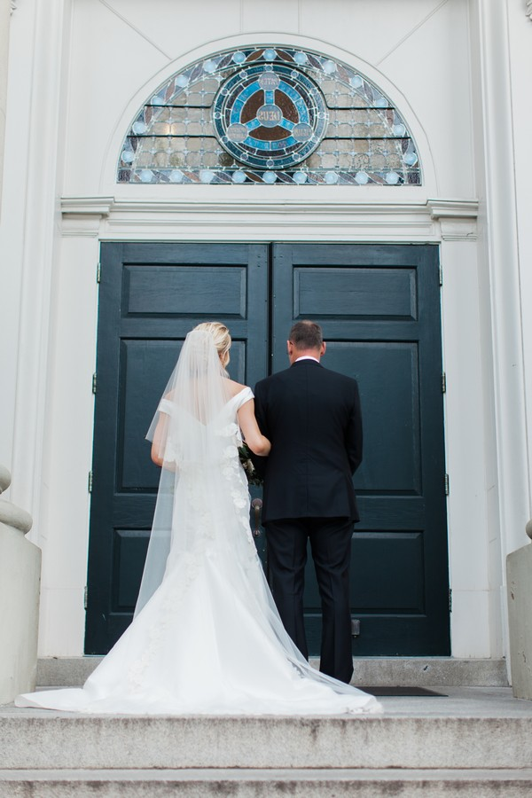 Father and daughter waiting at door to wedding ceremony venue