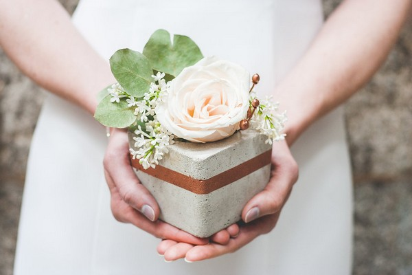 Bride holding concrete pot with flower in it
