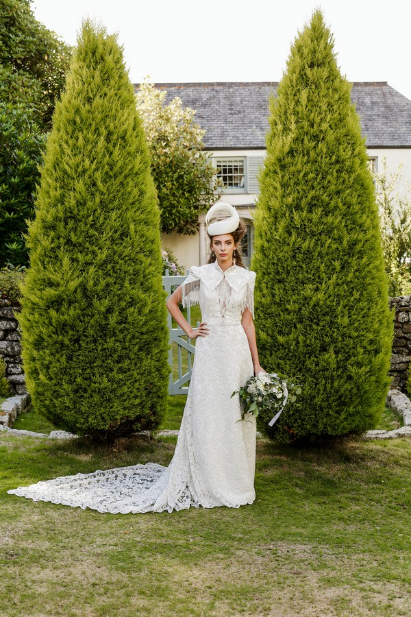 Bride with bridal hat standing in front of two tall bushes at Cosawes Barton
