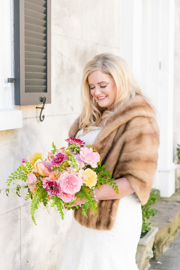 Bride with fur shrug holding colourful bouquet