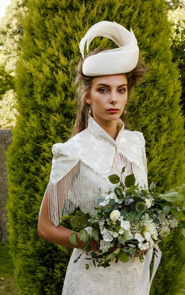 Bride wearing bridal hat holding bouquet