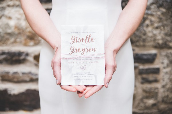 Bride holding wedding invitation with copper writing