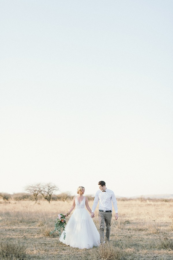 Bride and groom walking across Nambiti Private Game Reserve