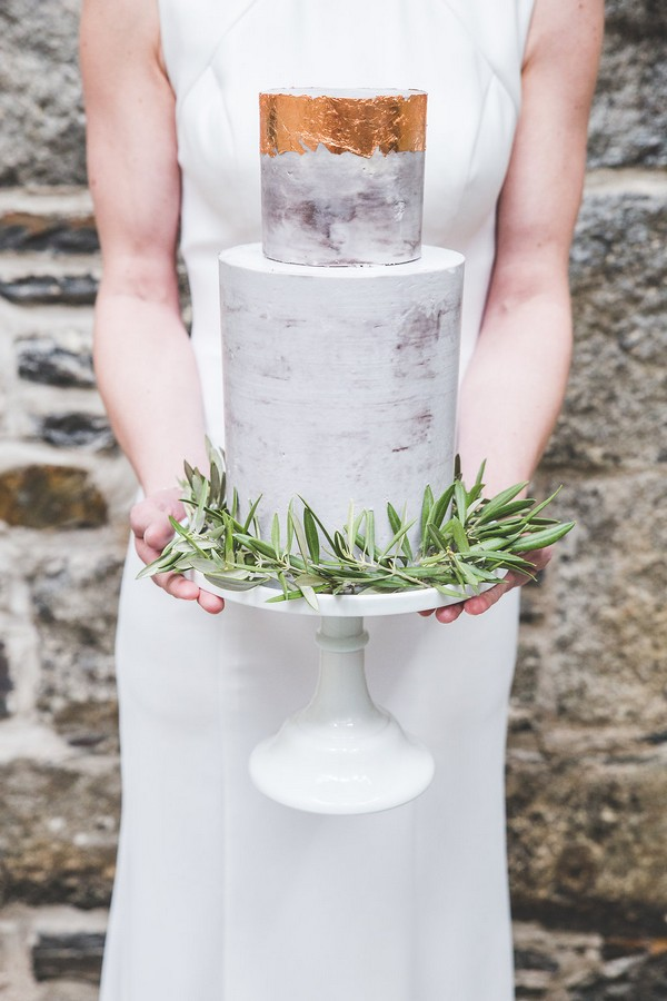 Bride holding wedding cake with copper top and rosemary around base