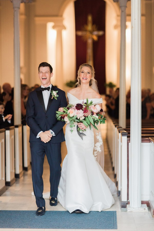 Groom with big smile as he leaves wedding ceremony with bride