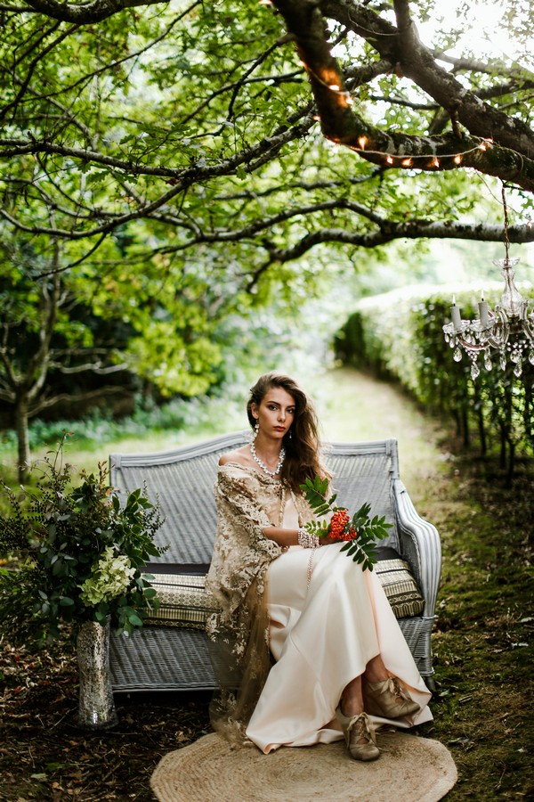 Bride sitting on couch in woodland at Cosawes Barton