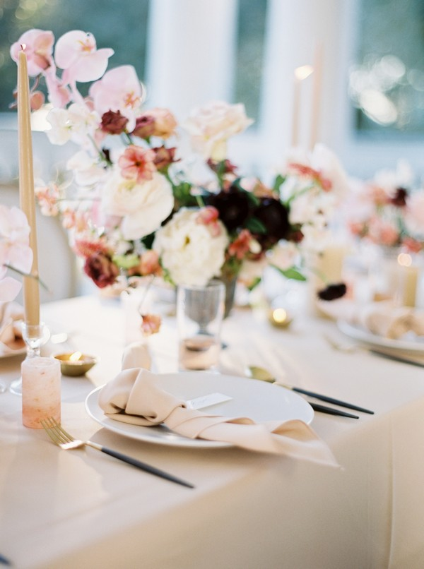Wedding place setting with blush flowers and tie napkin