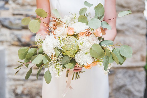 Bride holding peach, white and green bouquet with artichoke