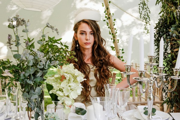 Bride with hat sitting at wedding table